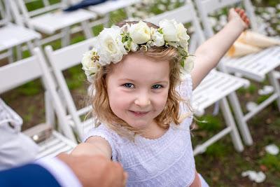 Niña vestida para una boda de la mano de su padre señalándole algo con una sonrisa