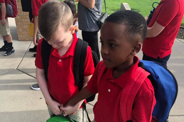 Boy holds hand of crying classmate with autism on first day of school