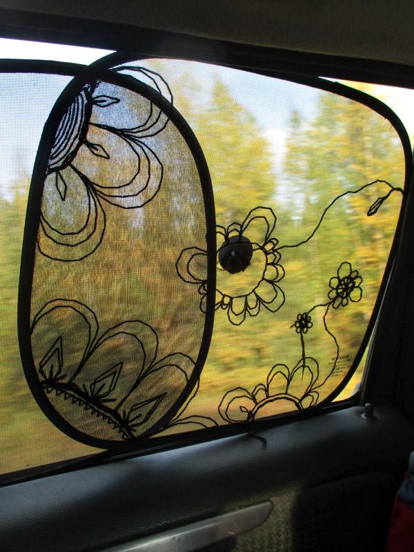 Mustalla langalla kirjailtu aurinkosuoja auton ikkunaan