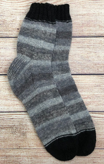 Socks knitted with DROPS Fabel Silver Fox and Black