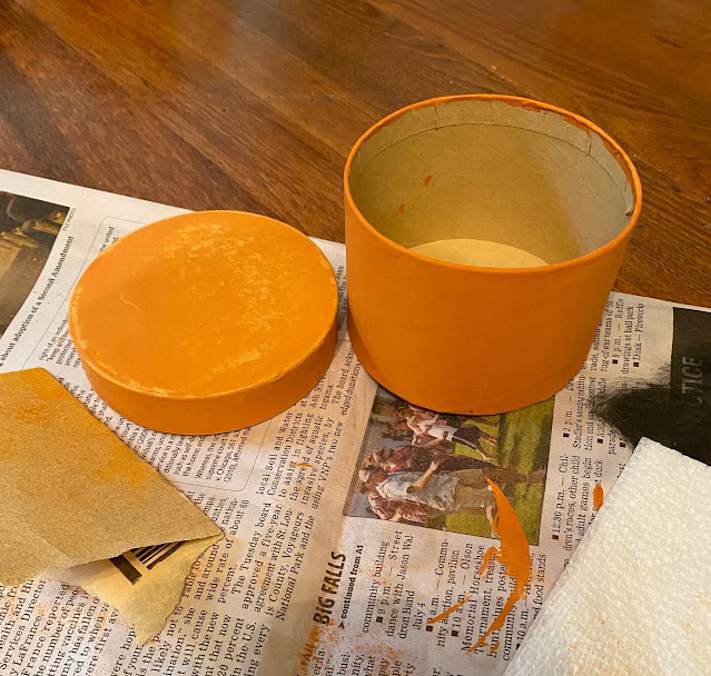 Photo of two round boxes painted orange being distressed with sandpaper