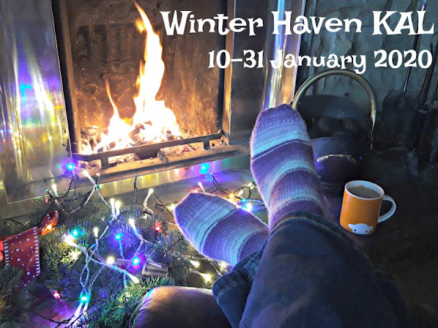 A photo showing a cosy winter scene.  To the bottom left is some winter greenery with fairy lights resting on it; in the centre is a pair of crossed legs and feet soaking up the warmth of the log fire which you can see in the background.  The person is wearing a pair of socks knitted in purple Winwick Mum Hidden Gem yarn.  To the right is an orange mug with the Herdy logo on it which has tea in it., and behind that is a coal bucket and some fire irons