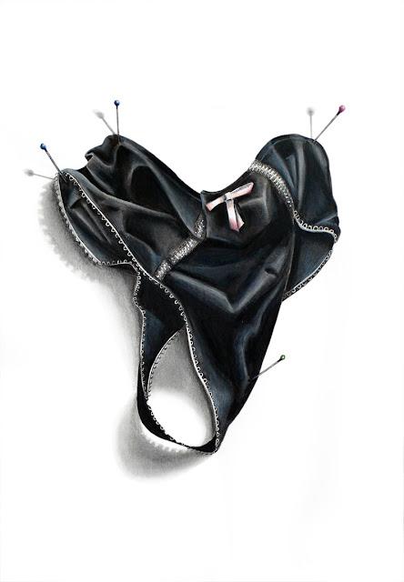 Tenu par des épingles à têtes colorées, un string noir avec un petit noeud rose en haut au centre.