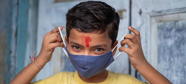 Un niño de 11 años en India muestra cómo ponerse correctamente una máscara para protegerse del COVID-19.UNICEF/Vinay Panjwani