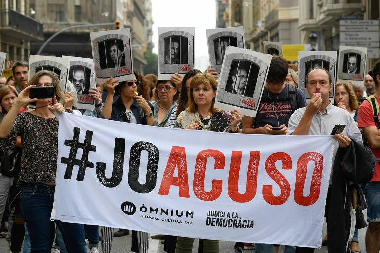 """Pessoas seguram cartaz com a frase """"eu acuso"""" em Barcelona, após sentença que condenou líderes separatistas catalães Lluis Gene/AFP"""