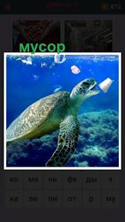 под водой плывет черепаха и вокруг неё один мусор в воде