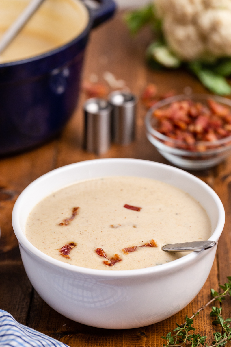 Closeup side view of Easy Cauliflower Cheese Soup in a white bowl with a large blue soup pot in the background on a wooden table.