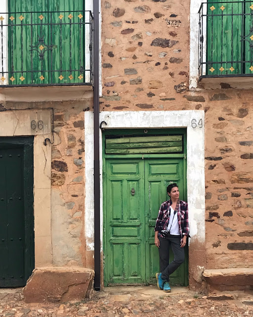 Chica apoyada en una puerta verde en Castrillo de los Polvazares