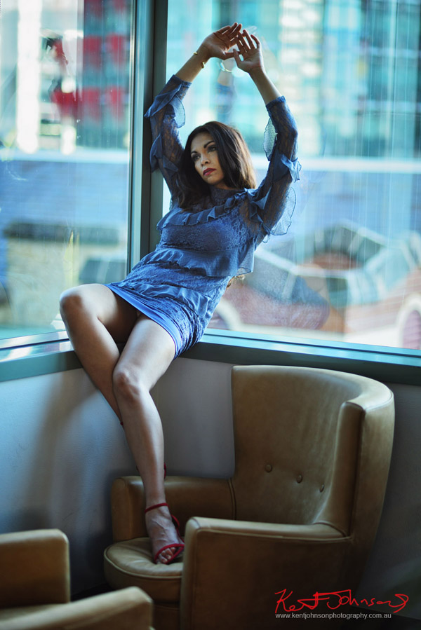 Long shot of a model in a corner window with beautiful long legs for a modelling portfolio. Photographed by Kent Johnson, Sydney, Australia.