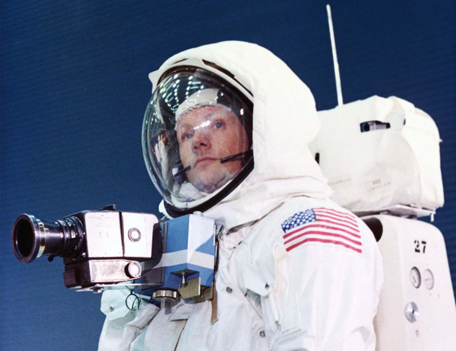 O comandante da Apollo 11, Neil Armstrong, treina no traje espacial que ele usará na superfície lunar. Uma câmera é anexada ao seu peito, dando-lhe pleno uso de seus braços; a mochila fornece oxigênio, pressurização e controle de temperatura.
