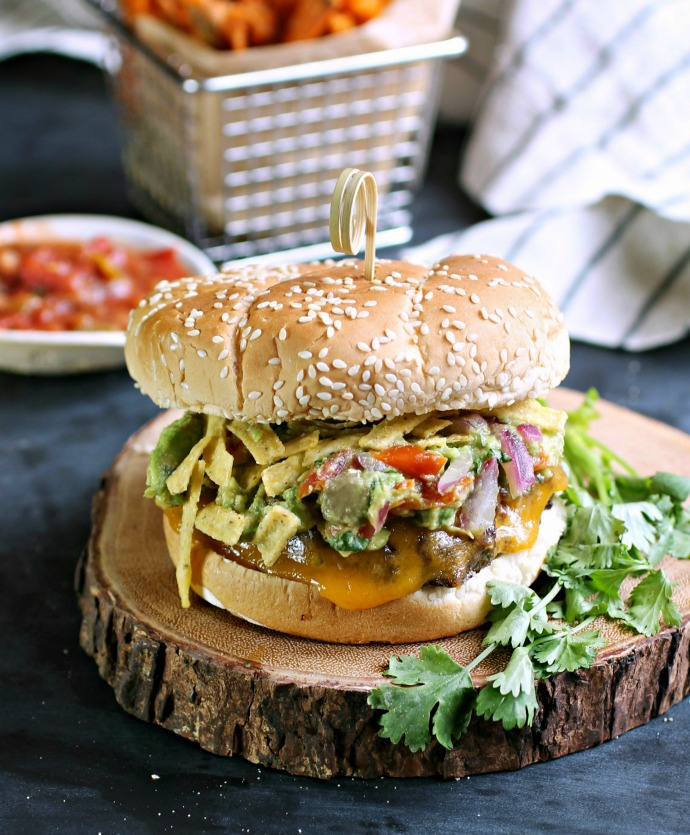 Recipe for a burger with southwestern flavors and topped with guacamole and crunchy tortilla strips.