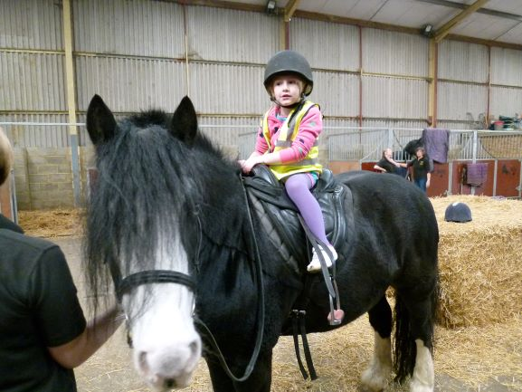 sasha sitting on a black horse