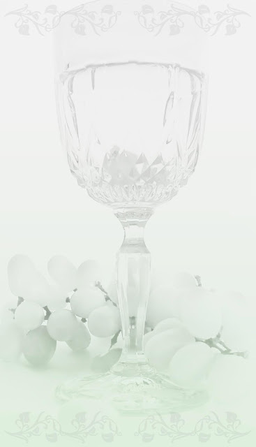 A cutglass wineglass with a handful of green grades on a lace background.