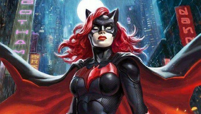 Mulher branca de cabelos ondulados vermelhos. Ela usa uma máscara com orelhas de morcego e seus lábios são vermelhos. Seu uniforme é preto com um morcego vermelho no peito e tem uma capa vermelha e longa em seus ombros.