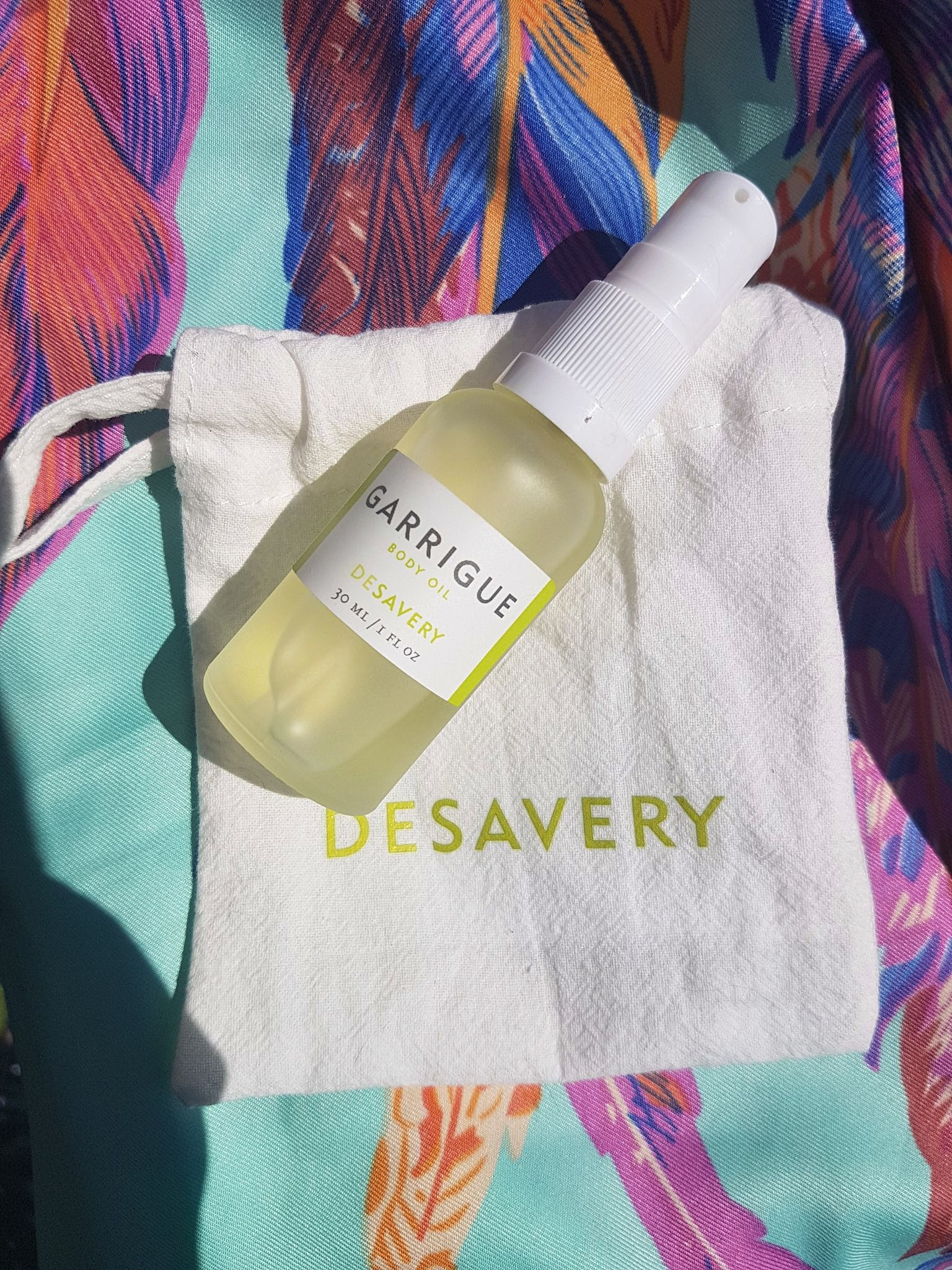 Desavery Garrigue Body Oil on top of a white linen pouch and a bright multi colour silk fabric