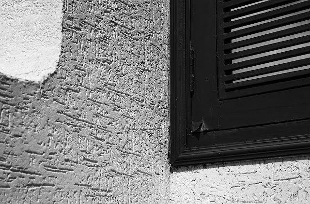 A Black and White Minimal Art Photograph of the Corner of a Window on a Textured Wall.