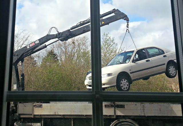 Car being lifted onto a flat bed with a crane