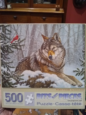 "500 piece jigsaw puzzle, ""Winter Friends,"" with wolf lying in snowy forest looking at red cardinal on tree"