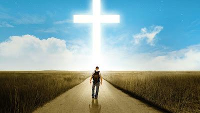 Hombre caminando hacia una cruz gigante por el campo