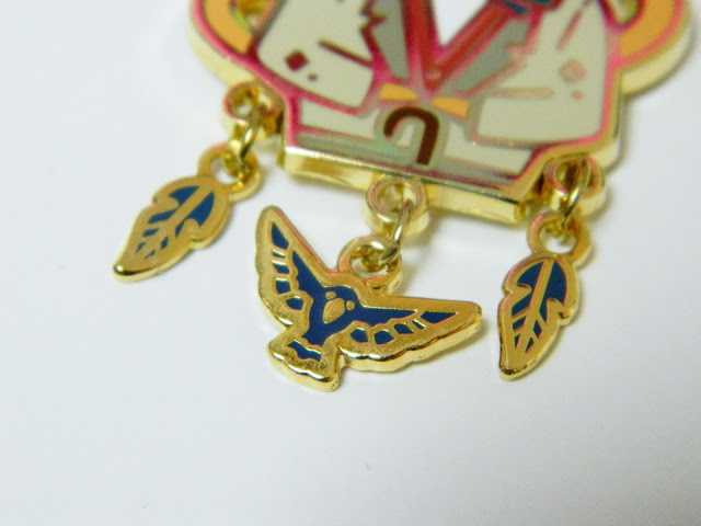 A photo of three charms on an enamel pin, two blue feathers and a blue crow