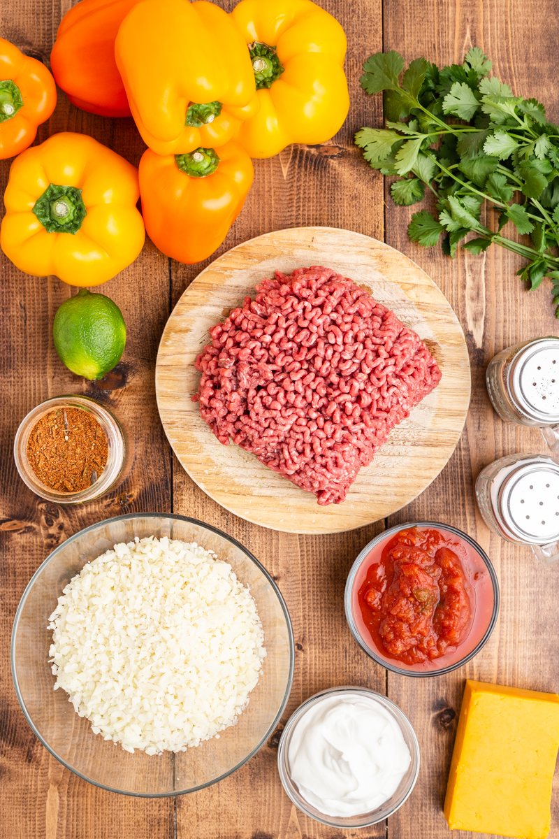Overhead photo of the ingredients needed to make Keto Slow Cooker Mexican Stuffed Peppers on a wooden table.