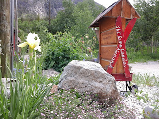 Exterior photo of flowers and wagon with crossed skis attached to Ski Town Condos sign.  Mountain in the background.