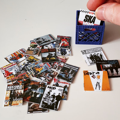 One twelfth scale modern miniature scootering and mod magazines next to a plastic crate containing a collection of records. A few are on the ground in front of the crate and a full-sized hand is pulling one out of the crate