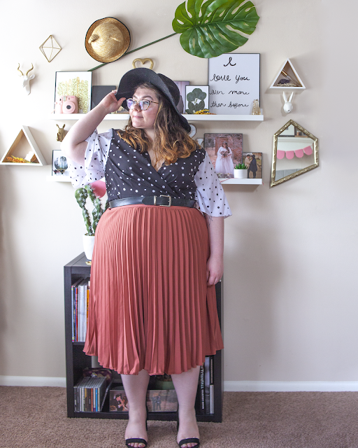 An outfit consisting of a black wide brim hat, white on black dotted wrap dress with black on white dotted sleeves tucked into a contessa colored pleated midi skirt and black strappy heels.