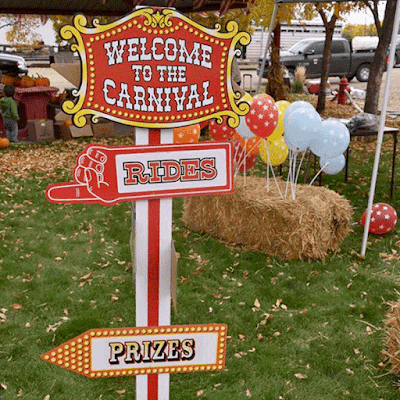 Sign for Carnival with signs pointing to rides and prizes