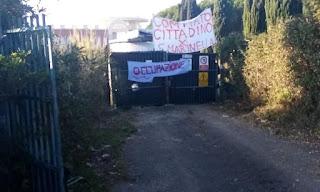 """Stradina maltenuta che porta a un cancello su cui sono due striscioni, uno """"Comitato Cittadino x Santa Marinella"""" l'altro """"Occupazione"""""""