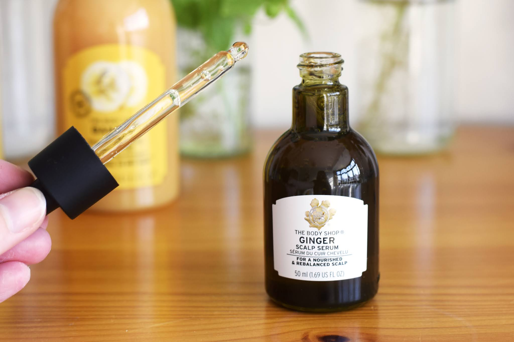 a small glass vial of body shop ginger scalp serum. The with pipet is off the vial and can be seen to the side.