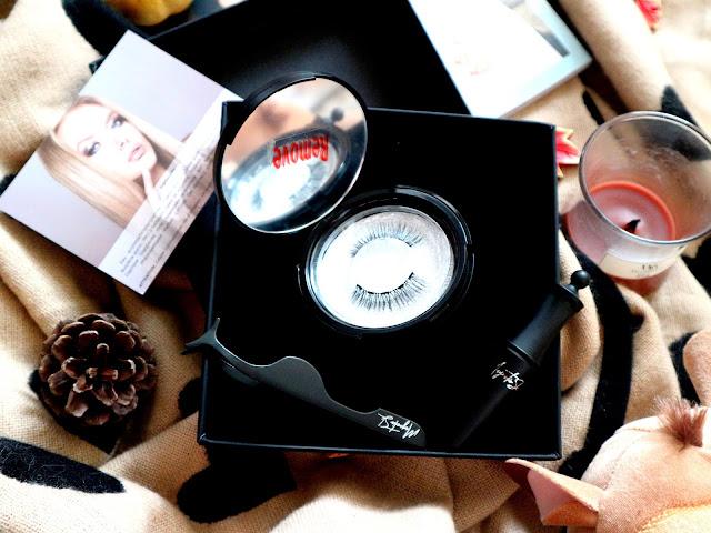 Une boite ronde qui contient une paire de faux-cils magnétiques et un eye-liner posé à côté.