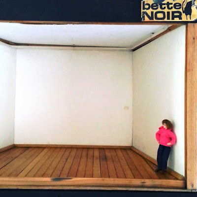 Modern miniature empty gallery with a doll standing assessing the space.