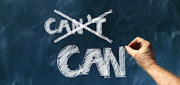 A persons hand crossing our the word can't and replacing it with can