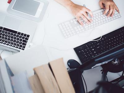 Persona manejando varios ordenadores