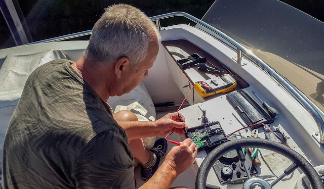 Photo of Phil checking the power to the radio's charging unit on the flybridge