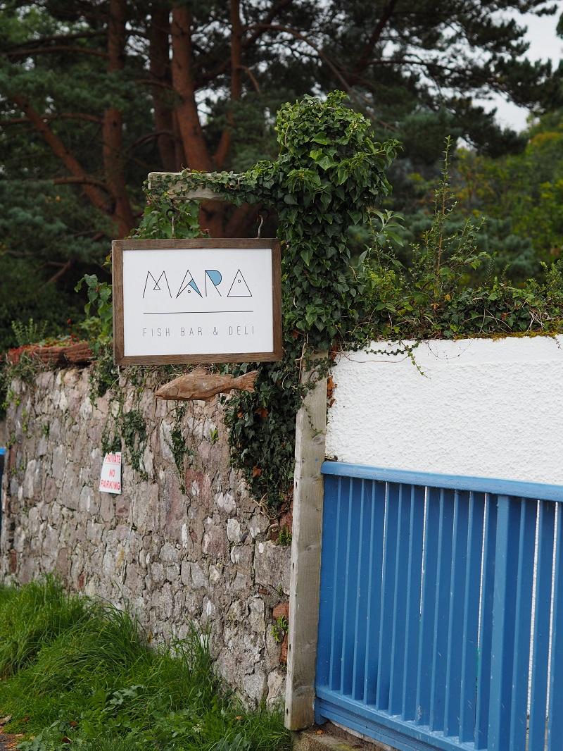 Mara Fish bar and deli sign among green foliage