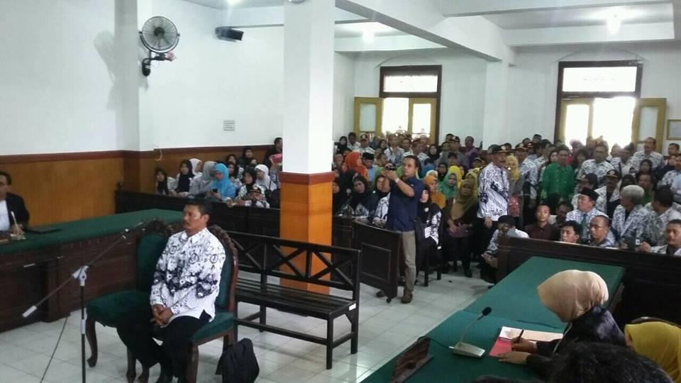 seorang guru duduk di kursi terdakwa