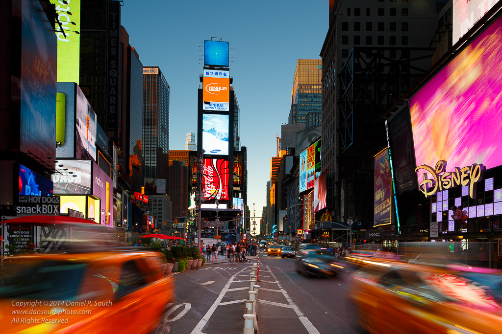 a photo of taxi cabs in motion in times square new york