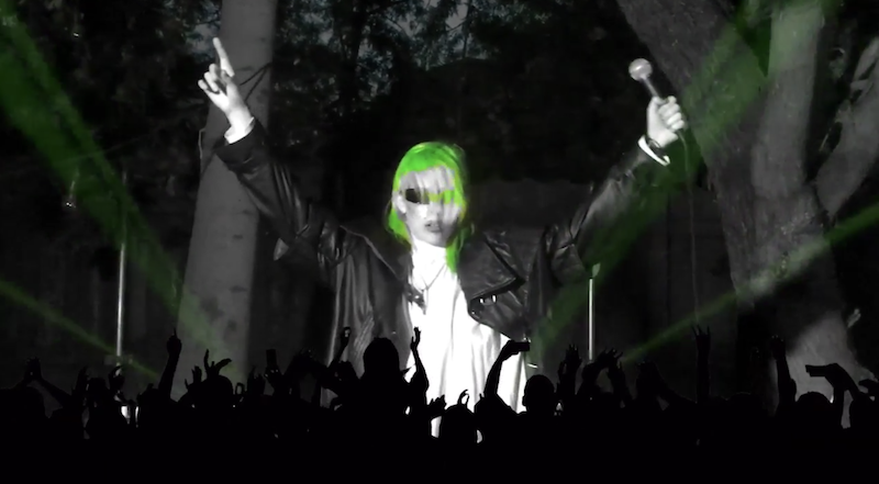 Dorian Electra performing behind a clipart silhouette of crowds of people