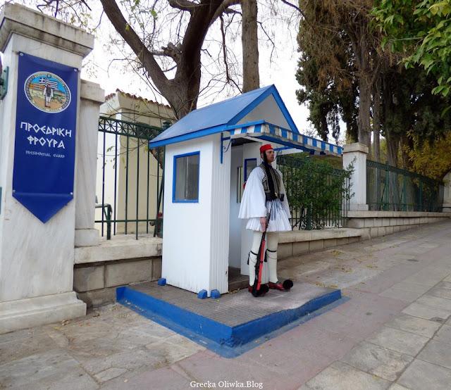 na ulicy biała budka z niebieskim dachem przy której pełni wartę ubrany w białą fustanellę, czerwoną czapkę  z karabinem w ręku grecki żołnierz Greckiej Gwardii Prezydenckiej. Ateny Grecja.