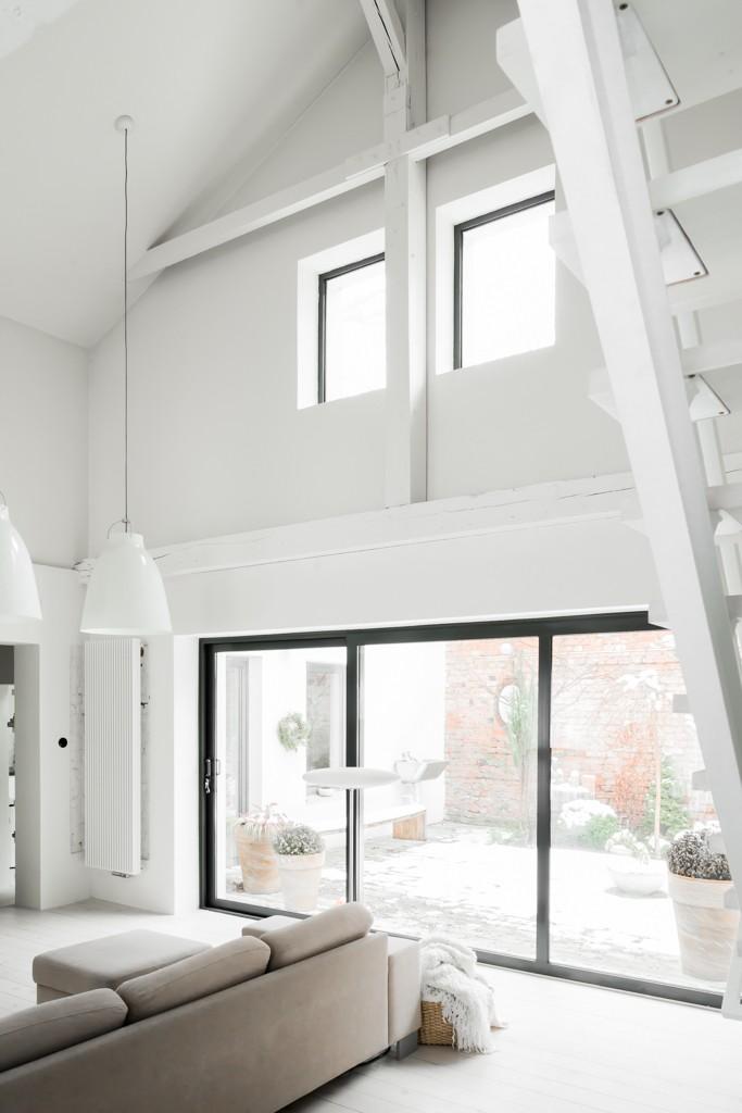 Amplio salón blanco con techos muy altos y lámparas colgantes Caravaggio