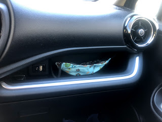 A small compartment in the dashboard of the car, just the right size for a mask.