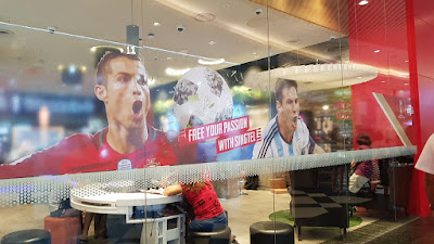 Singtel outlet with pictures of footballers and the slogan Free your Passion with Singtel. Taken at Jurong Point on 13 May.