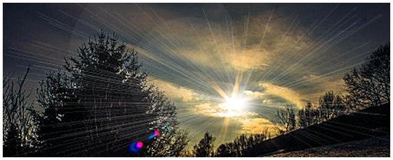 Auringon kirkkaita säteitä kevättaivaan pilvien välistä.