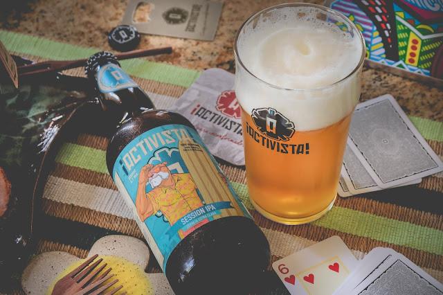 Garrafa de cerveja deitada ao lado de copo e baralhos