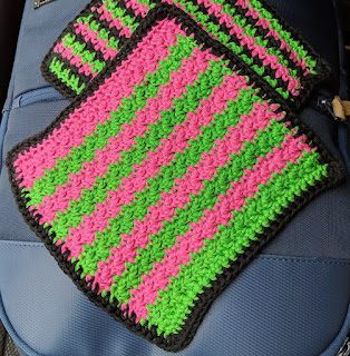 Two crochet face washer laying on a bag, the top one in pink and green with a black border.