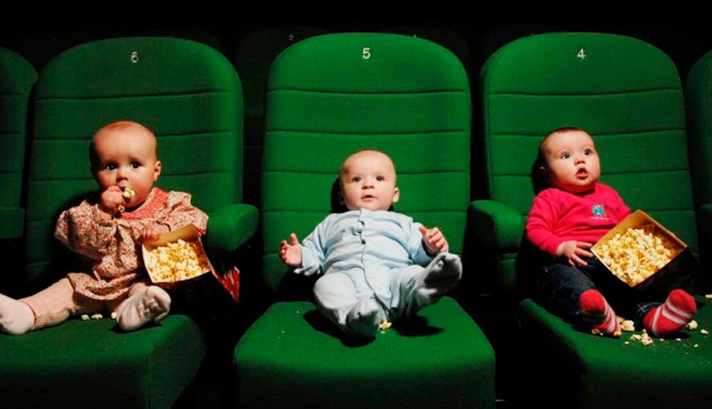 Dois bebes sentados em cadeiras de cinema verde, um comendo pipoca