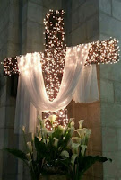 In a church setting, a cross with small whie lights covering it and also an altar cloth made of white satin