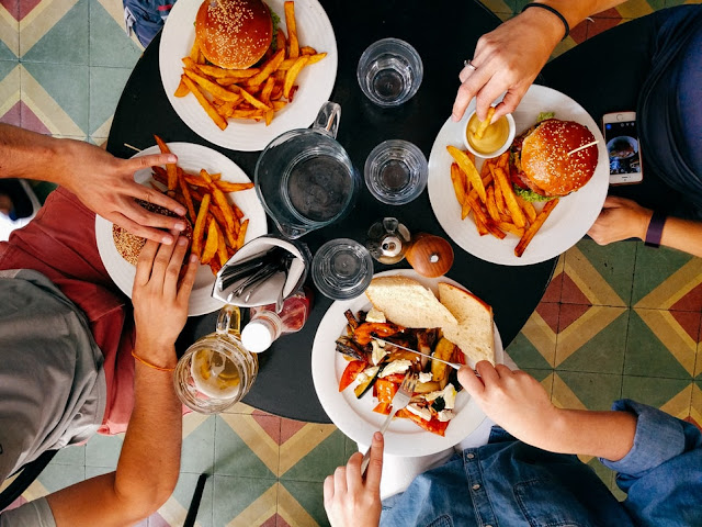 Overhead photo of a people eating burgers and fries at a round table